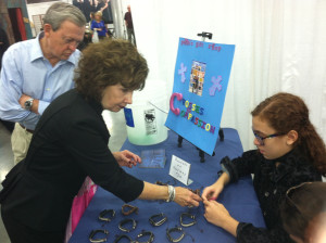 Gabrielle selling bracelets to help buy water filtration buckets for children in foreign countries via Compassion International. - #NQC2013